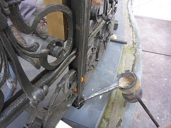 Das Geländer wurde vor Ort zusammengebaut und zur Versenkung der Steher in der Bodenplatte des Balkons eingebleit. Dazu wird die Position angezeichnet, vorgebohrt und eine exakt bemessene Vertiefung ausgemeißelt. Anschließend wird Blei in einer Bleipfanne vor Ort eingeschmolzen und in diese quadratische Vertiefung zu dem jeweiligen Steherende eingegossen, verdichtet und damit fix mit der Bodenplatte verankert.