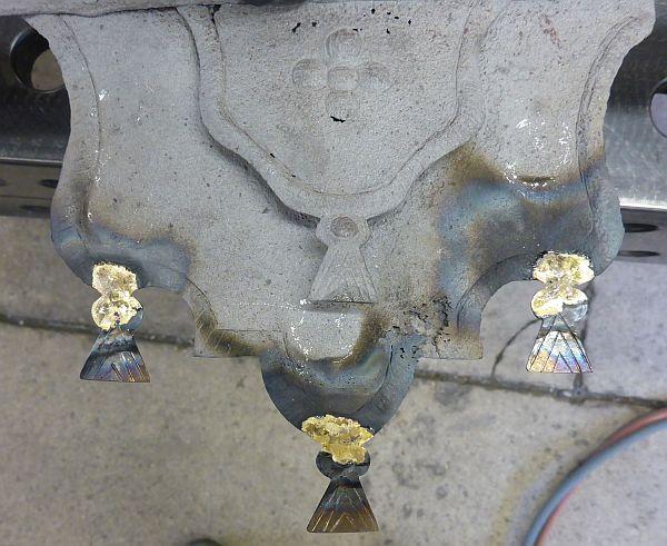 An einigen Kartuschen fehlten die stilisierten Quasten. Diese wurden nach historischem Vorbild neu hergestellt.Dafür wird ein Blechstück zugeschnitten, gekerbt und zugefeilt. Anschließend wurden die Blechquasten angelötet.