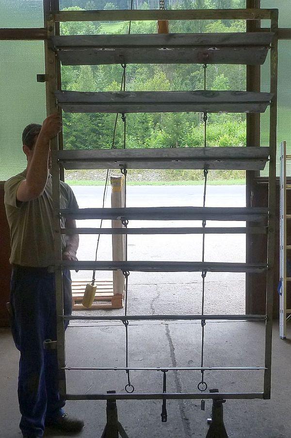 Ansicht eines technisch sanierten Lamellenteils. Neue Lamellen wurden eingesetzt, Rahmen, Eckverbindungen, Führungsschienen und-griff saniert, die Lamellenführung neu ausgerichtet und die Türbandrollen nachgeformt.