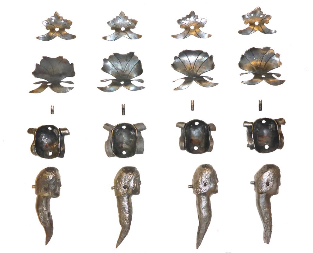 Alle Einzelteile (nach der Sanierung), die zum Kopf der Halbfiguren gehören: Kopfteil mit Halsteil und zwei als Nieten ausgebildete Schrauben, der Helmteil mit den beiden Doppelvoluten und schließlich zwei verschiedene Blätter zur Bekrönung. Die Teile werden in einer bestimmten Reihenfolge montiert.