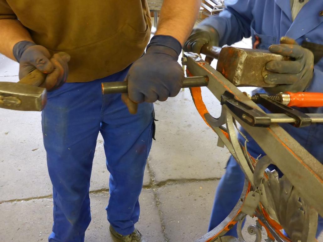 Die Abdeckleiste wird von Hand mit dem Grundgerüst des Geländers vernietet.