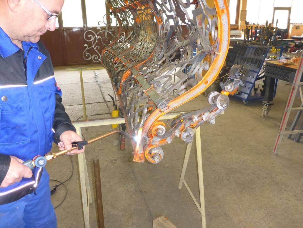 Die sanierte Halbfigur wird mittels Zapfen im glühenden Vierkantloch des Geländers vernietet.