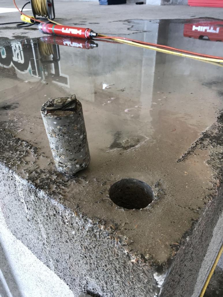 Ausgebohrter Bohrkern eines Eckstehers (hier aus Winkelstahl) neben dem Bohrloch.