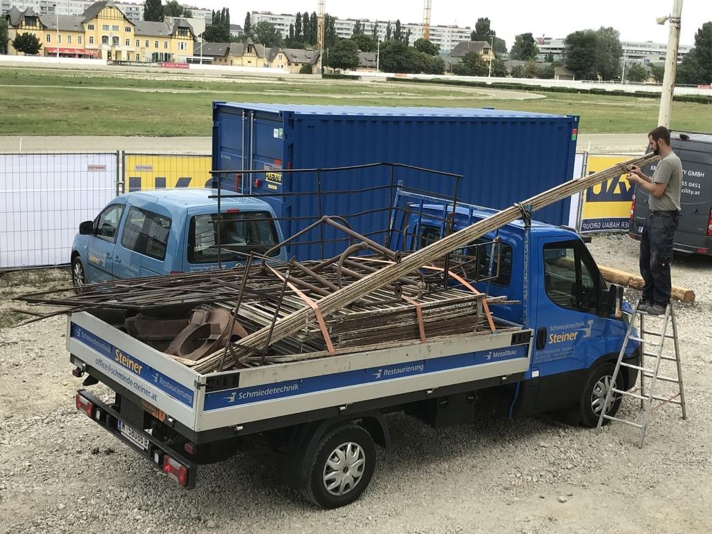 Beladen des firmeneigenen Pritschenwagens mit den zuvor beschrifteten Geländer- und Handlaufteilen. Hier: mit einigen Teilen der Zweikronen-Tribüne.