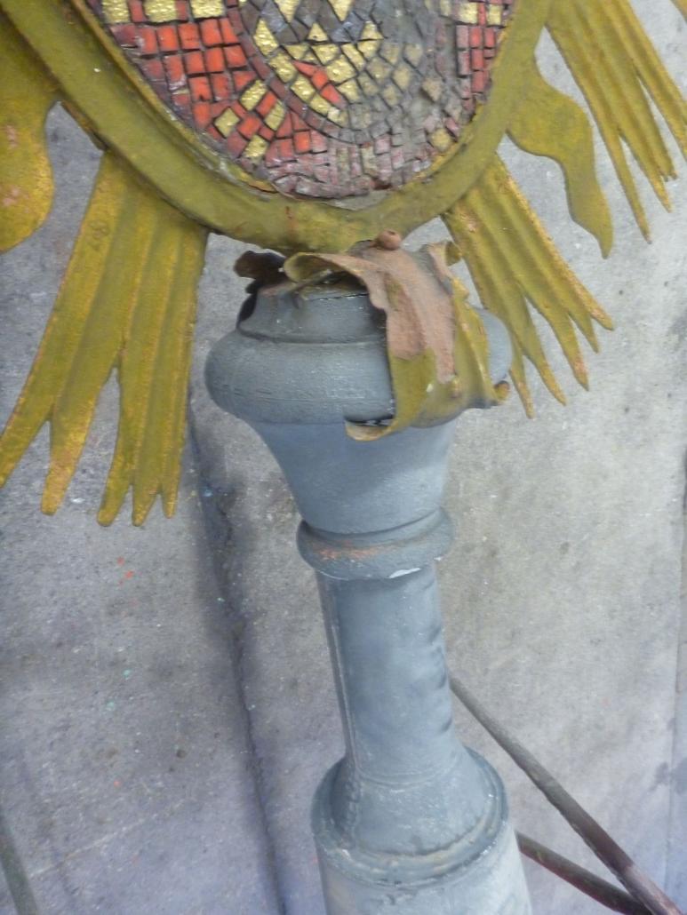 Der Träger des Strahlenkranzschildes besteht aus der Firstschmuckstange, die mit einem Schaft mit Sockel und einem Aufsatz mit zwei Zierblättern verkleidet ist.