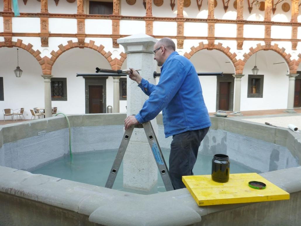 Letzte Deckbeschichtung der Wasserspeier vor Ort.