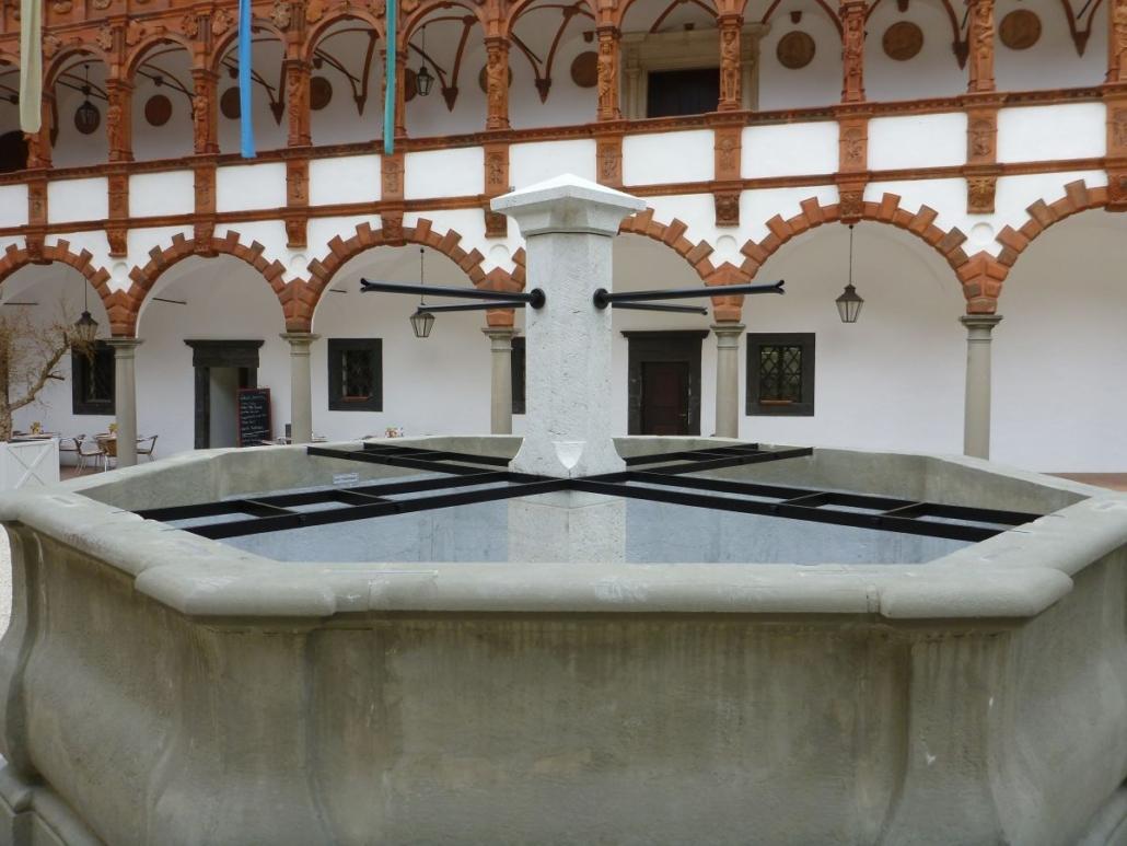 Ansicht auf den fertig restaurierten Brunnen. Die vier Auflagegitter stabilisieren den Mittelpfeiler mit den vier Wasserspeiern.