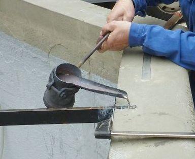 Detailansicht auf das Einbleien, dem Eingießen des flüssigen Bleis mittels Bleipfanne.